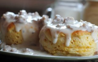 Biscuits covered in sausage gravy on a plate.